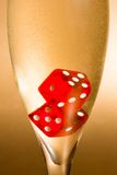 Detail of a flute with inside red dice and gold bubbles Stock Image