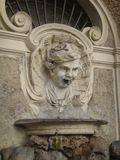 Detail of the fountain of the Botticella in Rome Italy. Representation of the head of an innkeeper or of a laborer with the characteristic lopsided beret that Royalty Free Stock Photography