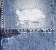Detail of Frayed Rip in Faded Blue Jeans Royalty Free Stock Images