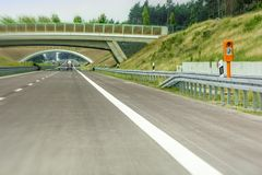 New section of motorway with emergency call and green bridge stock photography