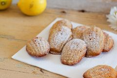 Detail of french sweet homemade pastry madeleines with lemon zest. Detail of french sweet homemade pastry dessert madeleines with lemon zest, next to lemons and Stock Photos