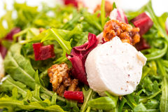 Detail of fresh arugula salad with beetroot, goat cheese and walnuts on glass plate  on white background, product photogra Stock Photo