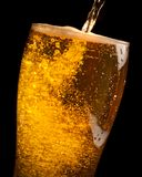 Detail of fresh beer pouring from bottle into glass Stock Photo