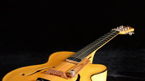 Detail of frets, string, body, mouth and bridge of typical classic spanish guitar rotating in black background. Classic Electric Guitar Jazz Rotating in stock video footage