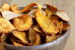 Detail of fried carrot and parsnip chips in rustic wood bowl. Royalty Free Stock Photography