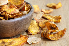 Detail of fried carrot and parsnip chips in rustic wood bowl. Stock Images