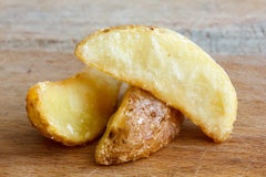 Detail of fried potato wedges  on rustic wood board. Stock Photos