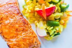 Detail of fried salmon fish with rice and vegetables Stock Images