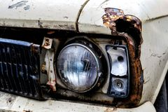 Detail of the front headlight of an old car in garage Royalty Free Stock Photo