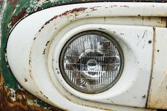 Headlight of a vintage car. Detail of the front headlight of a vintage car in garage Royalty Free Stock Image