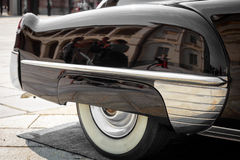 Detail of the front of the right rear of a black vintage car. Close-up of the front of the right rear of a black vintage car Stock Image