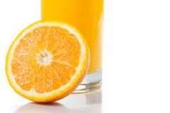 Detail of full glass of orange juice near half orange with space for text Stock Images