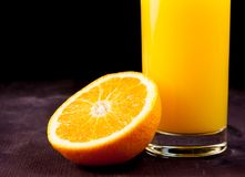 Detail of full glass of orange juice near half orange Royalty Free Stock Photography