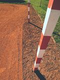 Detail of gate frame . Football or handball playground, light red clay. Red crushed bricks surface on ground Royalty Free Stock Photography