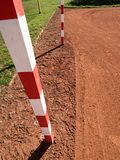 Detail of gate frame . Outdoor football or handball playground, light red clay. Red crushed bricks surface on ground Royalty Free Stock Photo