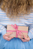 Detail of girl holding present behind back stock image
