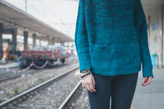 Detail of a girl posing in a railroad station Royalty Free Stock Image