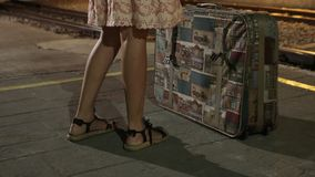 Detail on girl at train station with suitcase during night. Girl with suitcase waiting for her train on the platform in the station during the night Royalty Free Stock Images
