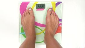 Detail girl weighing herself, on white, top view stock video
