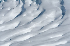 Detail of glacier flow and crevasses covered by snow in winter stock photography