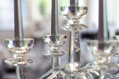 Detail of glass candelabra with silver candles. Blurry background.  stock image