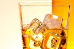 Detail of a glass of drink like whisky with ice Stock Photo