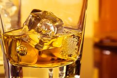 Detail of glass of whiskey with ices near bottle on table with reflection, warm atmosphere Stock Images