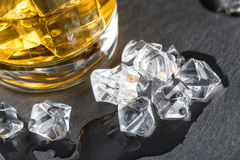 Detail of glass of whiskey and melted ice cubes Royalty Free Stock Photos