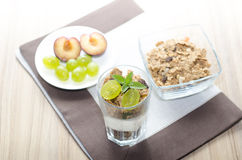 Detail of glass with yogurt, cereals, fruit and mint, plums Stock Photography
