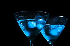 Detail of glasses of fresh blue cocktail with ice on black background royalty free stock photography