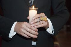 Detail of the godfather,s hands holding a candle and pacier. Detail of the hands of the christening godfather who wears dark suit and white shirt with cufflinks Stock Photos