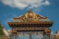 Detail of golden iron gate and fence lavishly decorated under sunny blue sky in Paris. stock photos