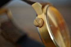 Detail of a golden watch with indented gold-plated crown as a symbol of time or exactness Stock Photos