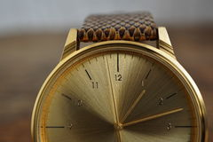 Detail of a golden watch with indented gold-plated crown as a symbol of time or exactness Royalty Free Stock Photos