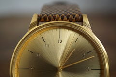 Detail of a golden watch with indented gold-plated crown as a symbol of time or exactness Royalty Free Stock Images