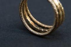 Detail of golden wedding ring on black background stock images