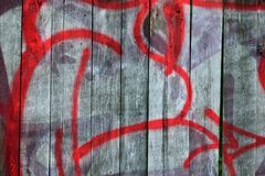 Detail of Graffiti on old wooden fence. Painted with red color Stock Photography
