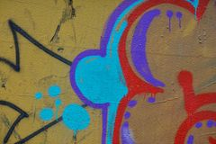 Detail of Graffiti on painted wall. Detail of Graffiti on the wall, yellow, blue, red and black Royalty Free Stock Images