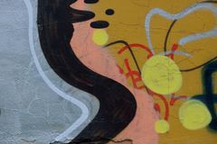 Detail of Graffiti on painted wall. Detail of Graffiti on the wall, yellow, pink, grey and black Stock Images