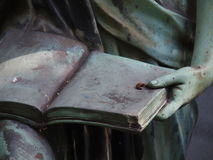 Detail of a grave stone statue. Holding a book Royalty Free Stock Image