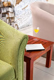 Detail of green armchair with table, book and cokctail Royalty Free Stock Photo