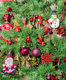 Detail of green Christmas (Chrismas) tree with colored ornaments, globes, stars, Santa Claus, Snowman Stock Image