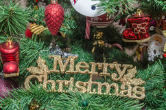 Detail of green Christmas (Chrismas) tree with colored ornaments, globes, stars, Santa Claus, Snowman. Red boots, shoes, candles, bells, white transparent Stock Photo