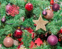 Detail of green Christmas tree with colored ornaments, globes, stars. Santa Claus, Snowman, red boots, shoes, candles, bells, white transparent angels, snow Stock Photos