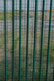 Detail of green fence guarding French ferry terminal. Royalty Free Stock Image