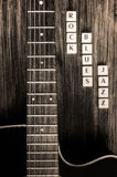 Detail of guitar and signs rock blues jazz in vintage style. Monochrome detail of guitar and signs rock blues jazz in vintage style Stock Photos