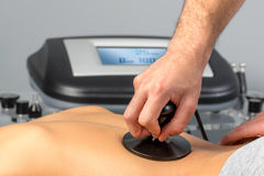 Detail of hand applying electrotherapy on female spine. stock image