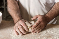 Detail on hand baker kneading dough on a black board with flour powder. The concept of baking and pastry shops. Royalty Free Stock Images