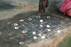 Detail of the hand of a boy playing a game with shells at the village of Eticoga in the island of Orango in Guinea Bissau. West Africa royalty free stock image