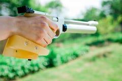 Detail on hand holding custom made grip of sport air pistol stock photos